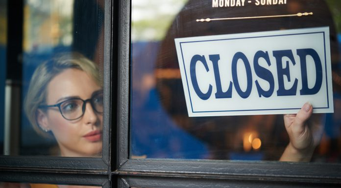 shop owner turning closed sign